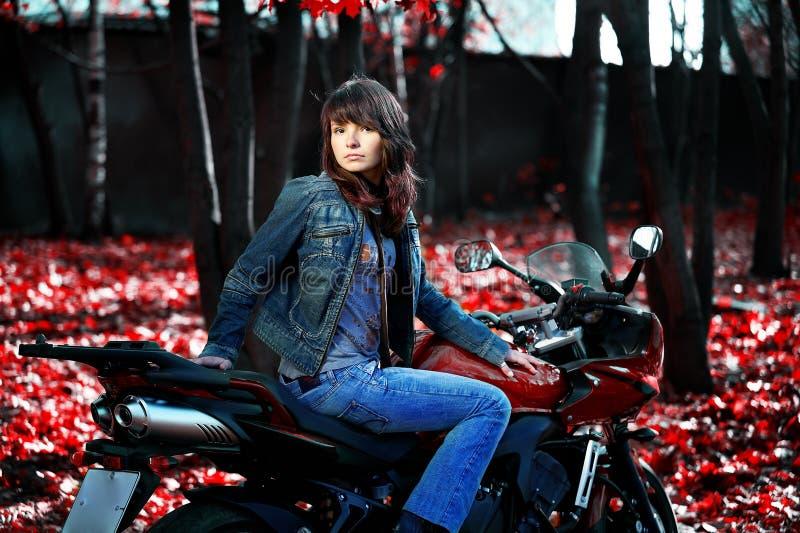 A menina misteriosa em uma motocicleta vermelha fotografia de stock
