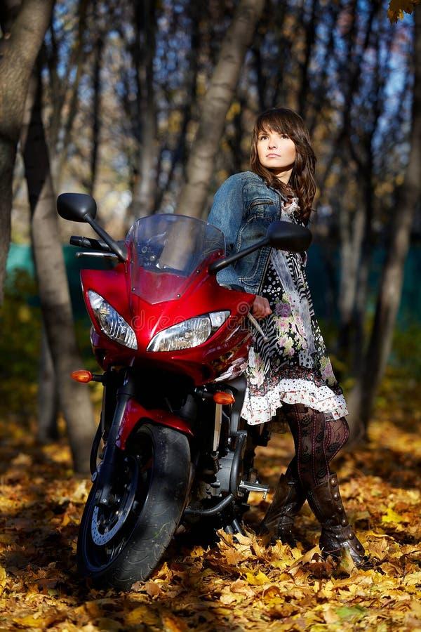 A menina misteriosa sobre uma motocicleta vermelha fotos de stock