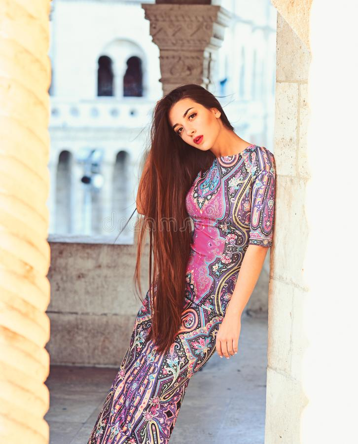 Menina ? moda bonita nova que levanta na rua da cidade do ver?o em um dia ensolarado Aturdindo o vestido violeta vestindo da mulh foto de stock