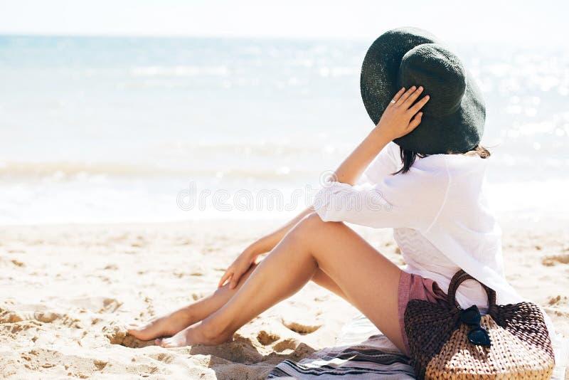 Menina ? moda do moderno no chap?u que senta-se na praia com saco da palha e que bronzea-se perto das ondas do mar F?rias de ver? fotos de stock royalty free