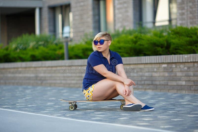 Menina ? moda mais o tamanho que senta-se em um longboard imagens de stock royalty free