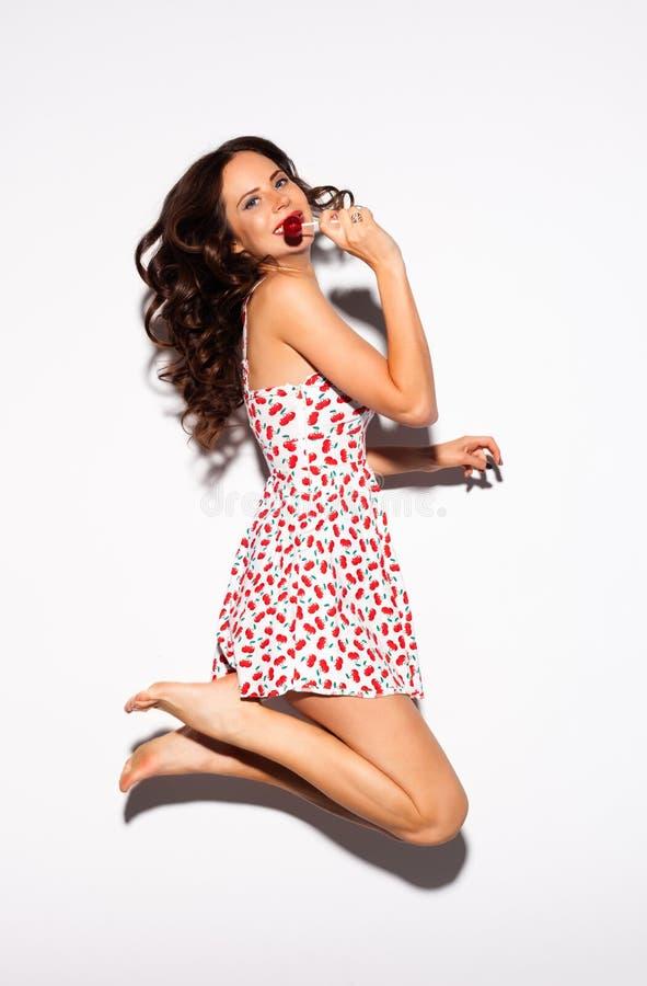 Menina modelo adolescente bonita de Brunette no vestido branco que salta no fundo branco com pirulito vermelho indoor Mulher feli imagem de stock royalty free