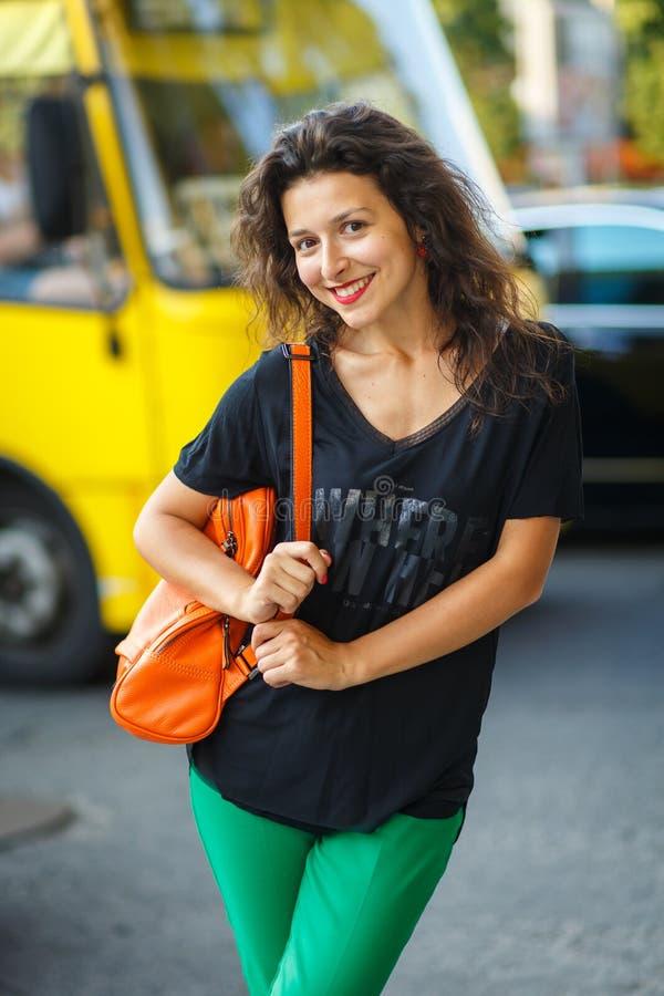 Menina modelo blackhaired bonita que levanta para a promoção de pano e de sacos no fundo das ruas da cidade imagem de stock