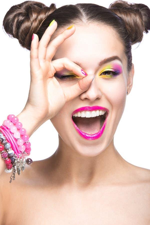 Menina modelo bonita com composição colorida brilhante e verniz para as unhas na imagem do verão Face da beleza Pregos coloridos  fotografia de stock