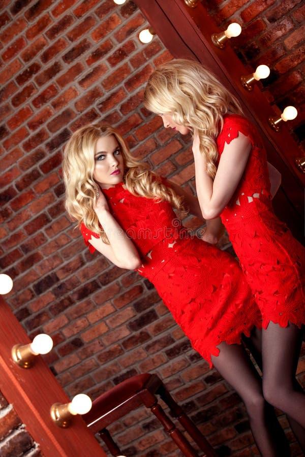 Menina modelo bonita em um fundo vermelho A beleza de uma mulher imagem de stock royalty free
