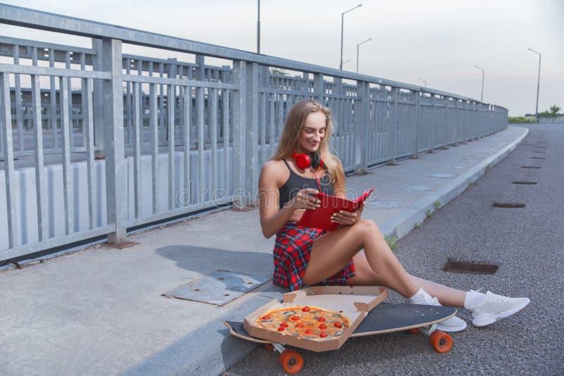 A menina modelo com pizza aprecia dispositivos vermelhos imagens de stock