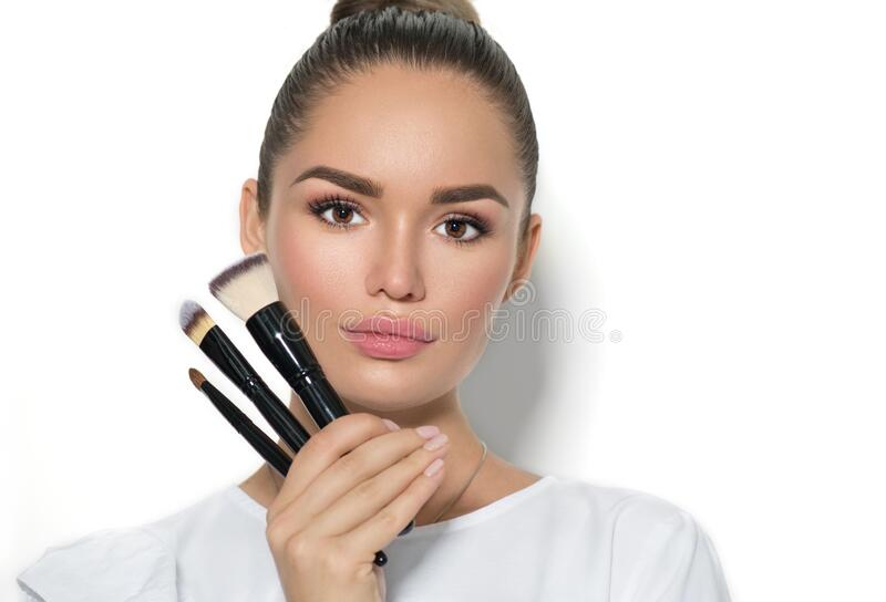 Menina modelo de beleza, maquiadora segurando pincéis de maquilhagem Linda jovem morena com pele perfeita foto de stock