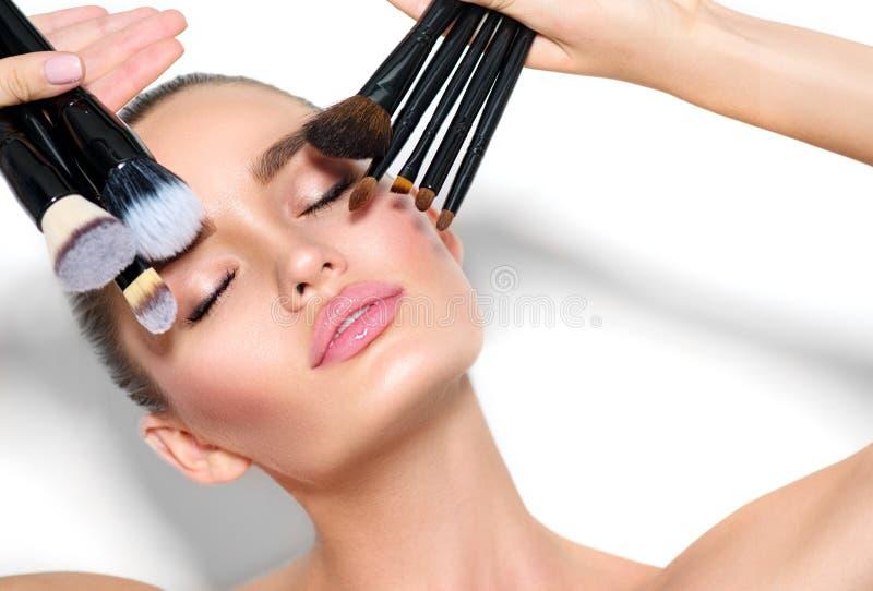 Menina modelo de beleza, maquiadora segurando um conjunto de escovas de maquilhagem Linda jovem morena com pele perfeita fotos de stock royalty free