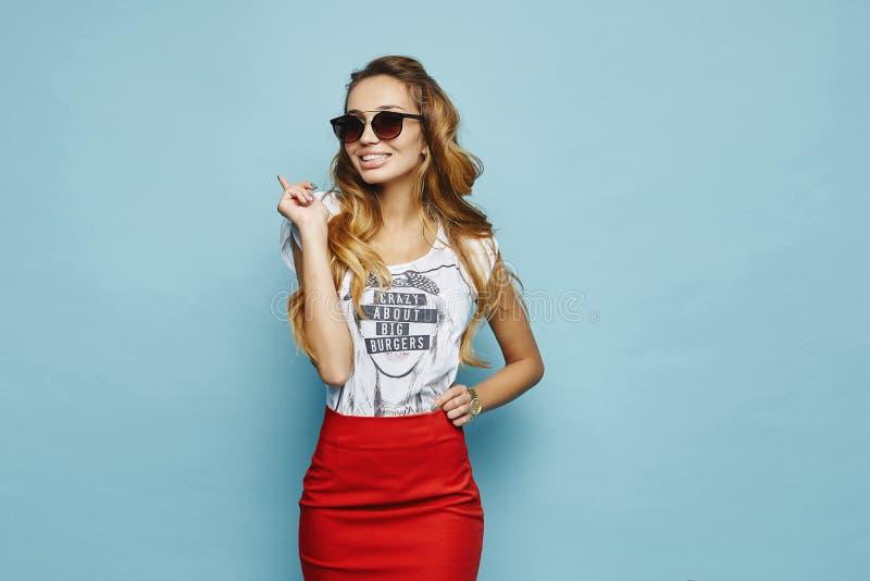 Menina modelo loura bonita, alegre e elegante no t-shirt branco, na saia vermelha e no sorriso à moda dos óculos de sol foto de stock