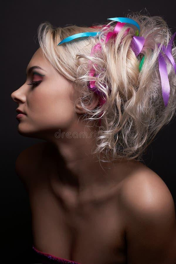 Menina modelo loura bonita com composição brilhante elegante e com as fitas coloridas em seu penteado à moda, isolado foto de stock