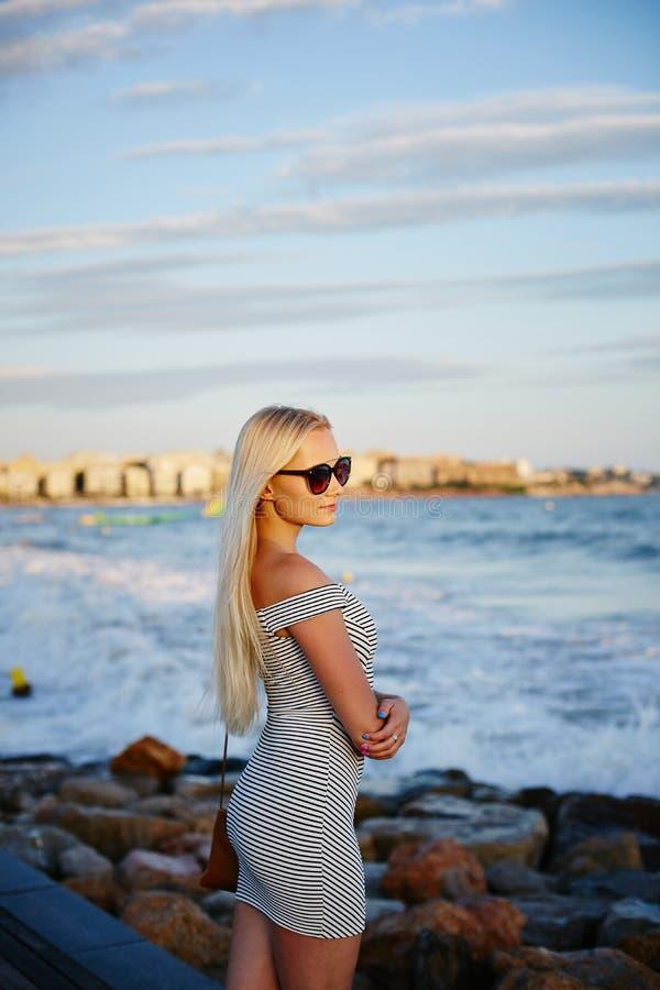 Menina modelo loura bonita e elegante com corpo 'sexy' no vestido curto listrado na moda e em óculos de sol à moda fotos de stock royalty free
