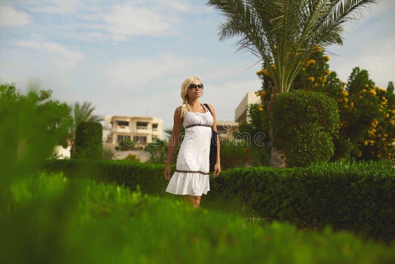 Menina modelo loura bonita e elegante, no vestido branco e nos óculos de sol, levantando fora fotografia de stock royalty free