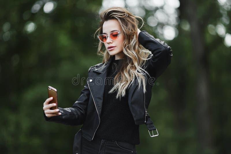 A menina modelo loura bonita e sensual elegante no casaco de cabedal preto, nas calças de brim e nele óculos de sol à moda toma a imagens de stock royalty free