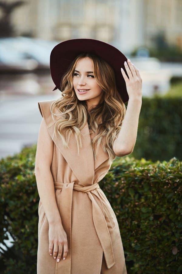 Menina modelo loura bonita e sensual elegante no revestimento sem mangas que ajusta seu chapéu à moda, sorrindo e levantando fora foto de stock