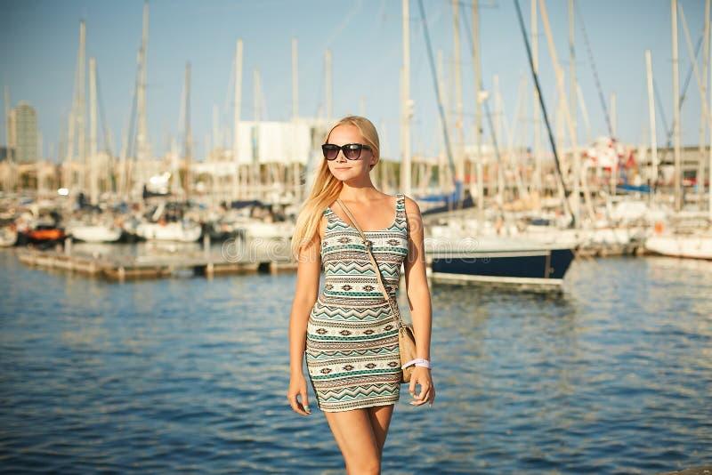 Menina modelo loura bonita e 'sexy' no vestido curto elegante e nos óculos de sol à moda que levantam na margem na frente do iate fotos de stock royalty free
