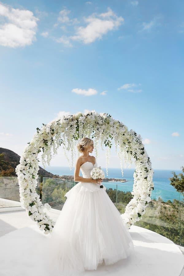 Menina modelo loura bonita no vestido de casamento branco com um ramalhete das flores em suas mãos que estão perto do círculo flo fotografia de stock royalty free