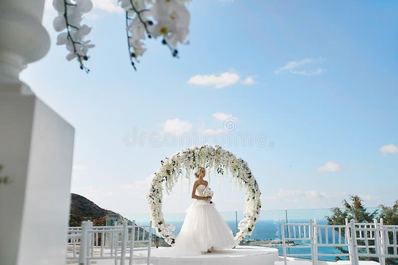 Menina modelo loura bonita no vestido de casamento branco com um ramalhete das flores em suas mãos que estão perto do círculo flo imagens de stock royalty free