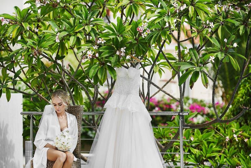 Menina modelo loura bonita, pechugóa e elegante com corpo 'sexy' em um peignoir branco e na roupa interior, com o ramalhete imagens de stock