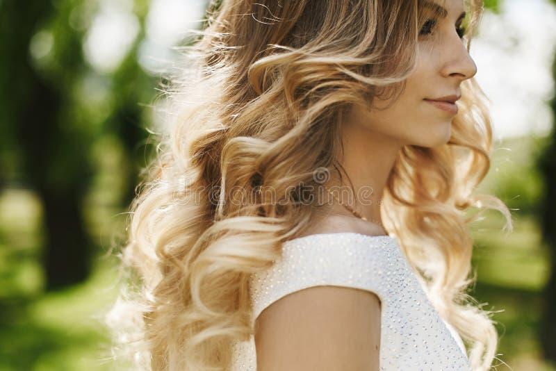 Menina modelo loura elegante e bonita com composição brilhante e com cabelo encaracolado, em uma parte superior brilhante à moda  fotografia de stock