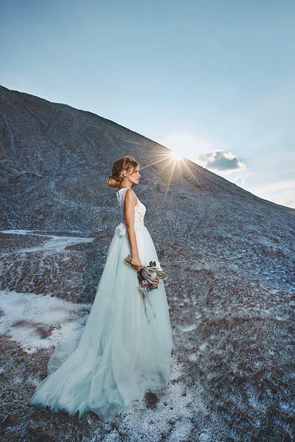 Menina modelo loura elegante e bonita com penteado da modelagem no vestido branco à moda do laço com o ramalhete de exótico fotografia de stock