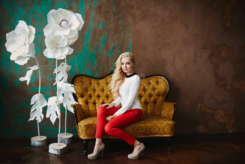 Menina modelo loura elegante, 'sexy' e bonita, na blusa e nas calças vermelhas, levantando no sofá no fundo luxuoso imagens de stock royalty free