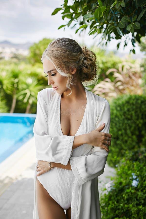 Menina modelo loura pechugóa sensual e 'sexy' com corpo perfeito no roupa de banho e no peignoir, suportes com olhos fechados e l fotografia de stock royalty free