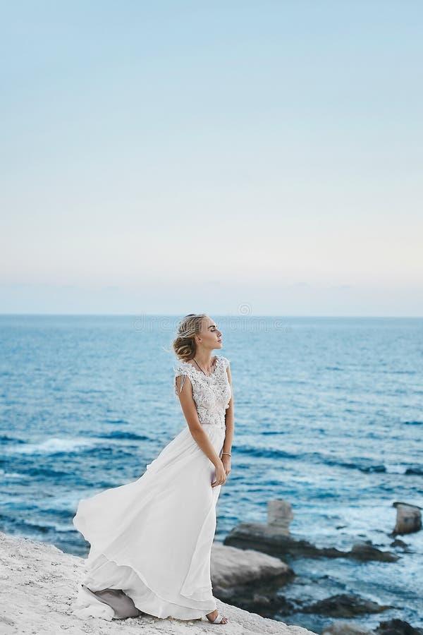 Menina modelo loura sensual e elegante com corpo perfeito no vestido branco à moda do laço com parte traseira despida, suportes n foto de stock