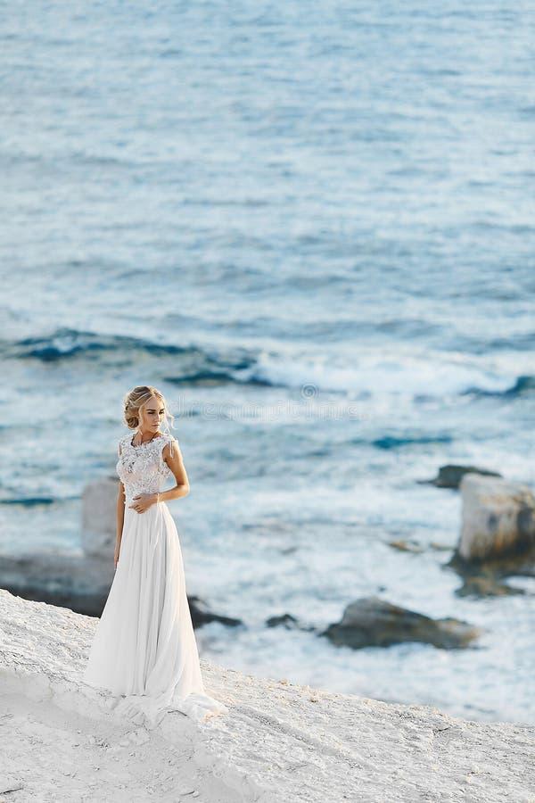 Menina modelo loura sensual e elegante com corpo perfeito no vestido branco à moda do laço com parte traseira despida, suportes n fotos de stock