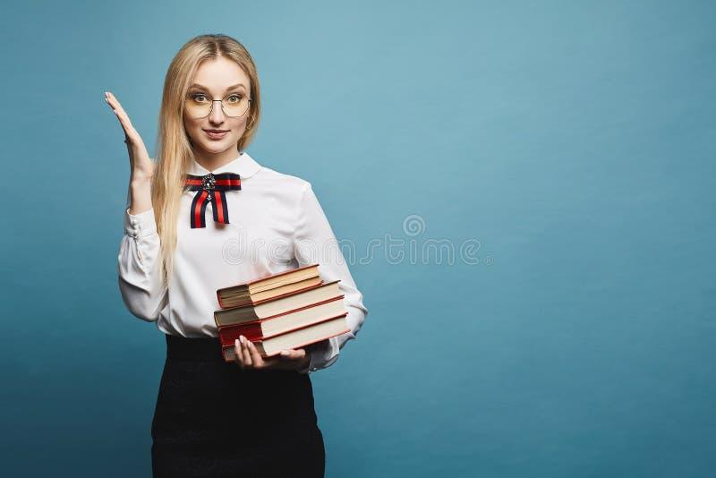 Menina modelo loura surpreendida bonita e elegante no eyewear, na blusa à moda e na saia preta do laço, com a pilha de foto de stock