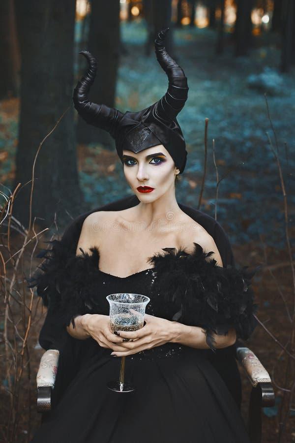 A menina modelo magro moreno bonita e elegante na imagem de Maleficent com vidro de vinho em suas mãos senta-se dentro fotos de stock royalty free