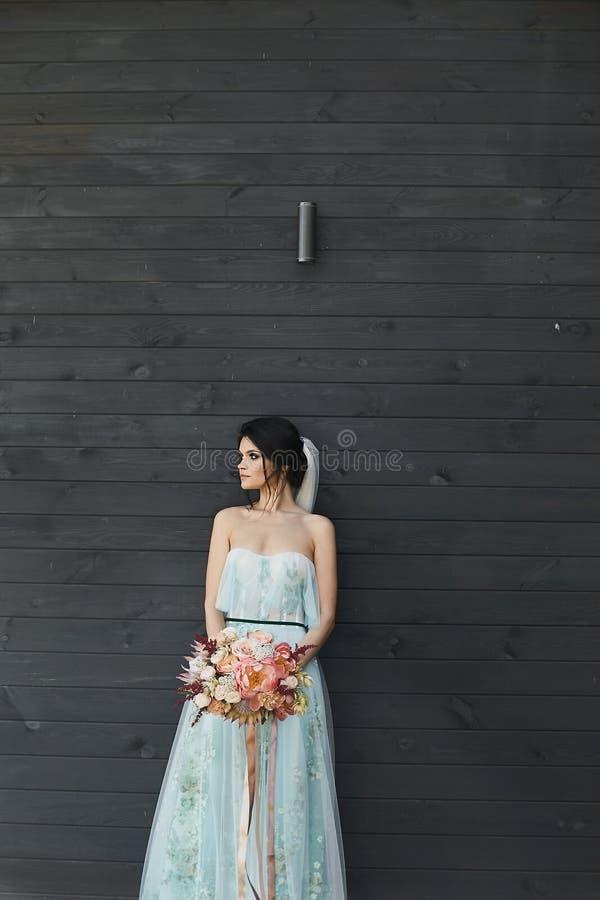 Menina modelo moreno bonita com composição brilhante no vestido elegante e no véu, com o ramalhete de fresco imagens de stock