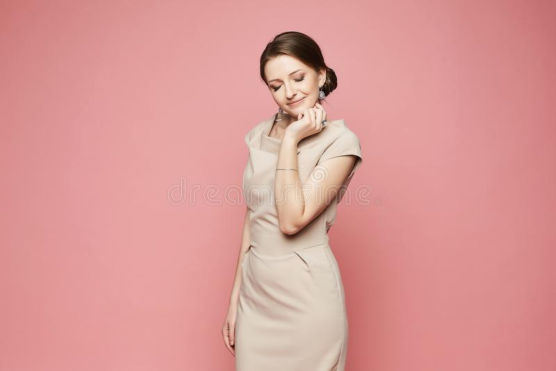 Menina modelo moreno bonita e elegante alegre com composição brilhante, no vestido bege e com brincos sorrindo e levantando a sag imagens de stock royalty free