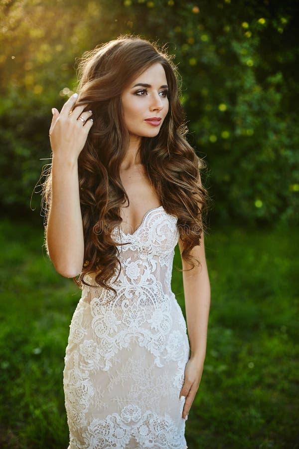 Menina modelo moreno bonita e elegante com composição brilhante e corpo 'sexy' no vestido à moda branco do laço que ajusta seu pe fotos de stock