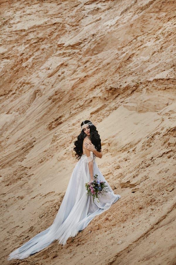Menina modelo moreno bonita e elegante com joia em sua cabeça no vestido elegante do laço que levanta no arenoso fotos de stock