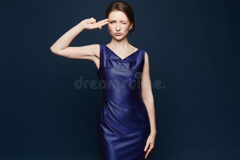 Menina modelo moreno bonita e elegante no vestido azul no fundo violeta, dentro imagem de stock