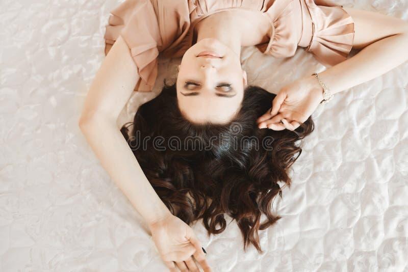 Menina modelo moreno bonita e sensual com composição delicada e com pele perfeita no vestido bege que levanta na cama em fotos de stock royalty free