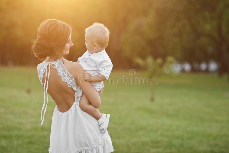 Menina modelo moreno bonita, mamã nova no vestido à moda branco curto que guarda em suas mãos seu bebê feliz bonito e fotografia de stock