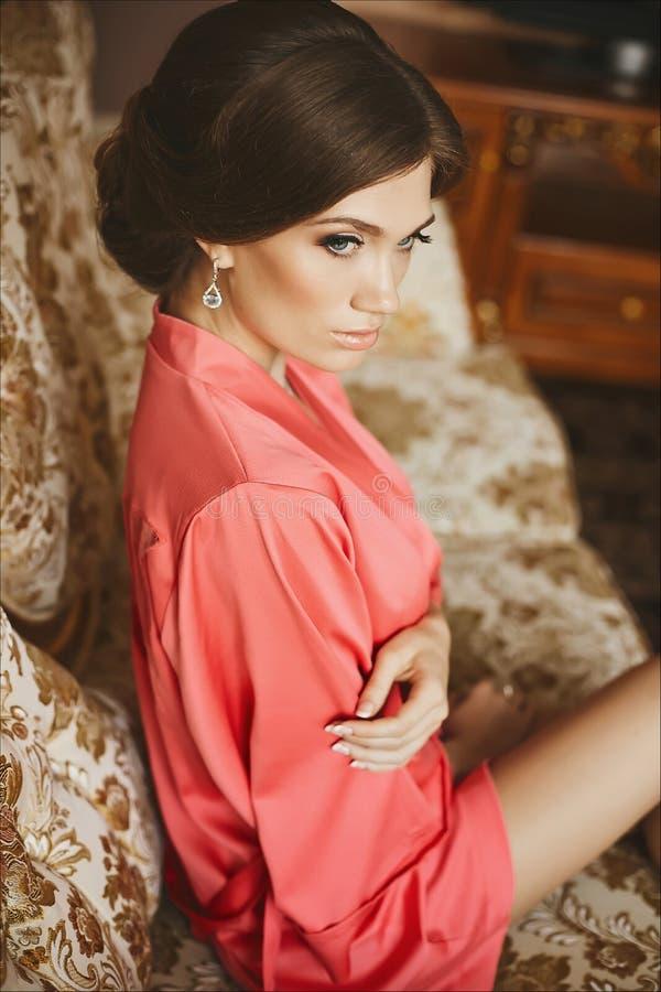 A menina modelo moreno elegante e bonita com corpo perfeito e com olhos azuis, em um peignoir cor-de-rosa, senta-se sobre foto de stock royalty free