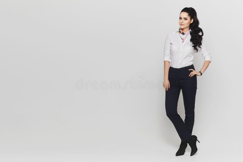 Menina modelo moreno elegante e bonita com um lenço em torno de seu pescoço na blusa branca e nas calças azuis dentro imagens de stock royalty free