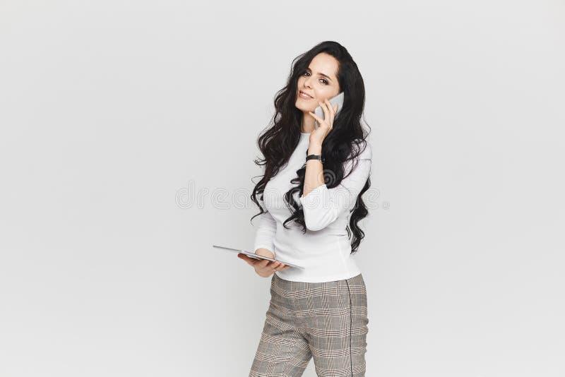 Menina modelo moreno feliz e bonita na blusa branca e nas calças de manta elegantes com a tabuleta nela imagem de stock