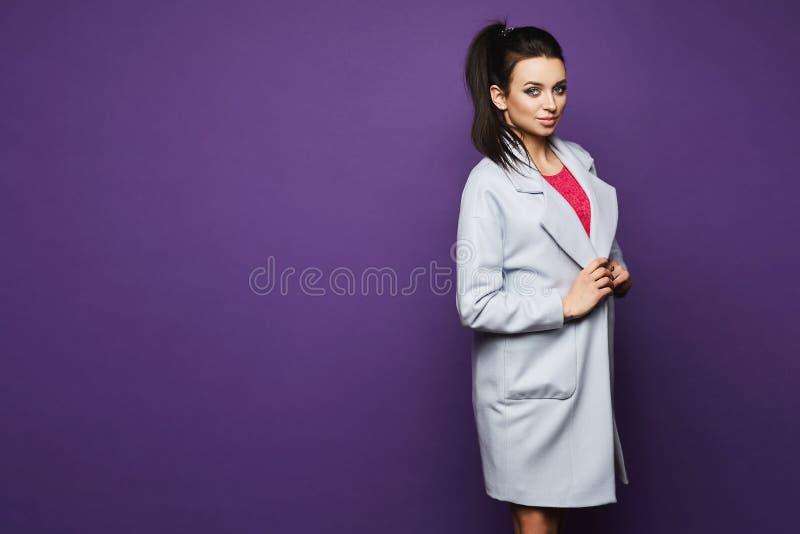 Menina modelo moreno 'sexy' e elegante com composição brilhante em um revestimento na moda e no vestido cor-de-rosa à moda curto  imagens de stock