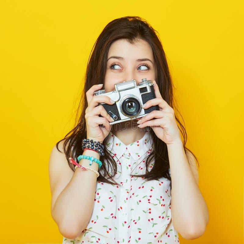 Menina moderna à moda que levanta com uma câmera retro nas mãos imagens de stock