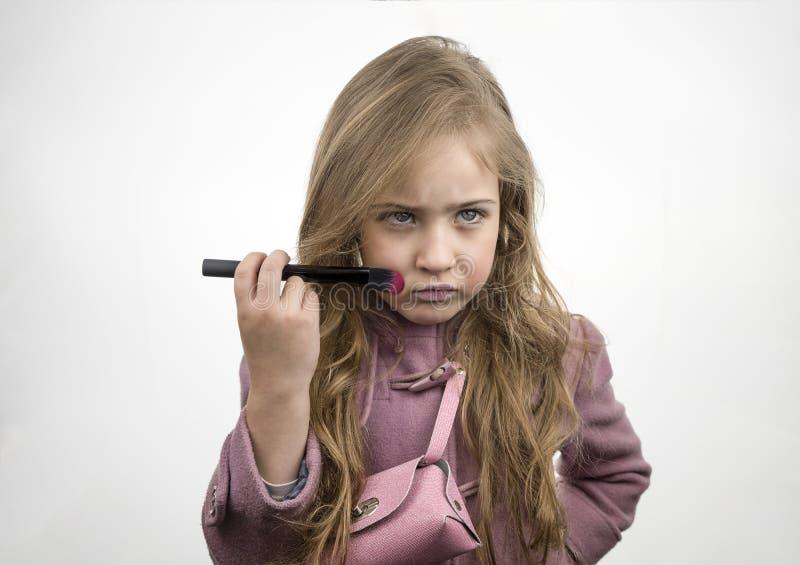 Menina moderna bonita que aplica a composição com uma escova grande e que olha fabulosa imagens de stock