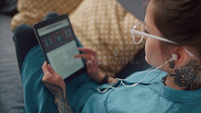 A menina moderna com fones de ouvido lê um eBook e uma tela dos rolos imagem de stock royalty free