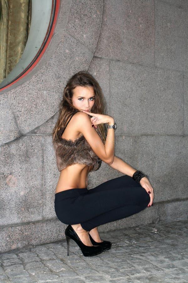 Menina modesta nos saltos altos que squatting imagem de stock