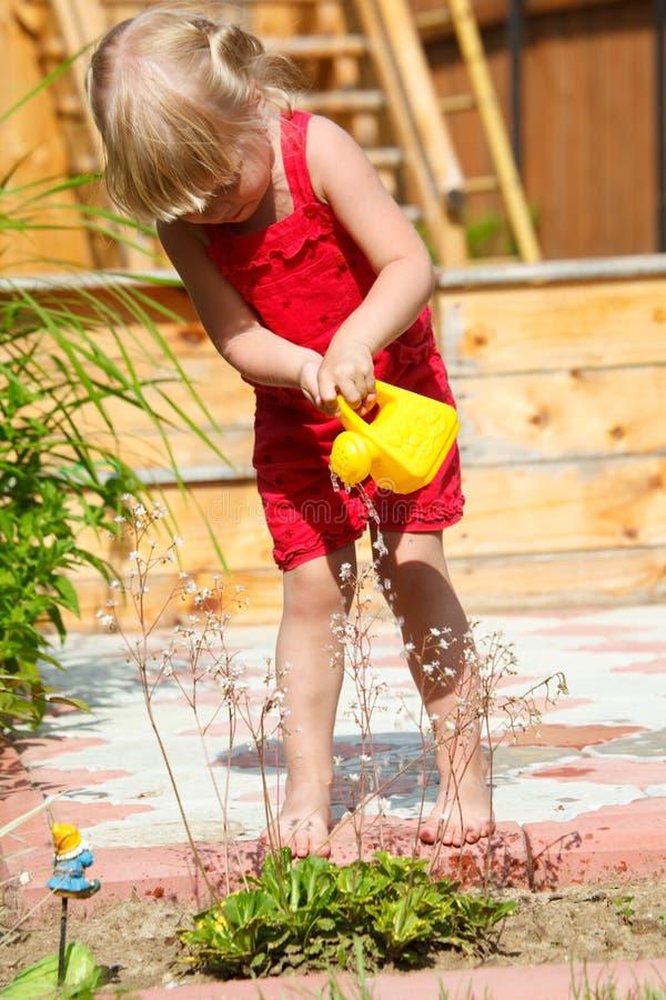 A menina molha flores de uma lata molhando do brinquedo imagem de stock royalty free