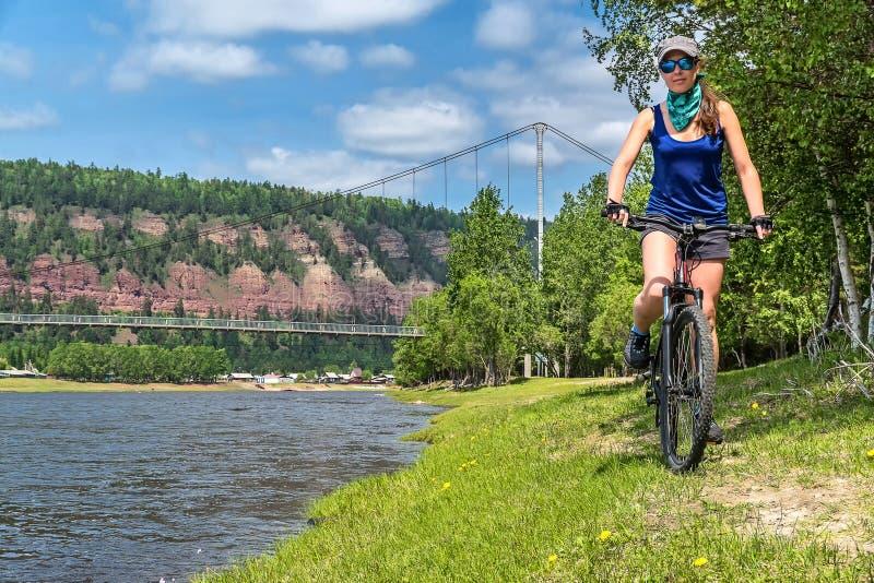 A menina monta a bicicleta no banco de rio fotografia de stock royalty free