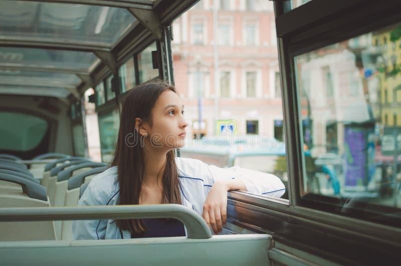 a menina monta no ônibus de excursão e olha para fora a janela St Petersburg, Rússia imagem de stock royalty free