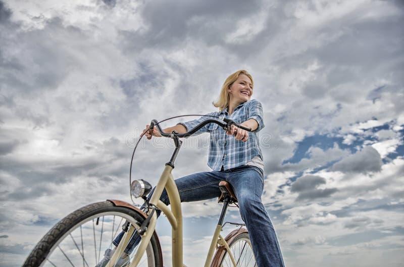 A menina monta o fundo do c?u da bicicleta A maioria de formul?rio satisfying do transporte do auto Despreocupado e satisfeito A  imagens de stock royalty free