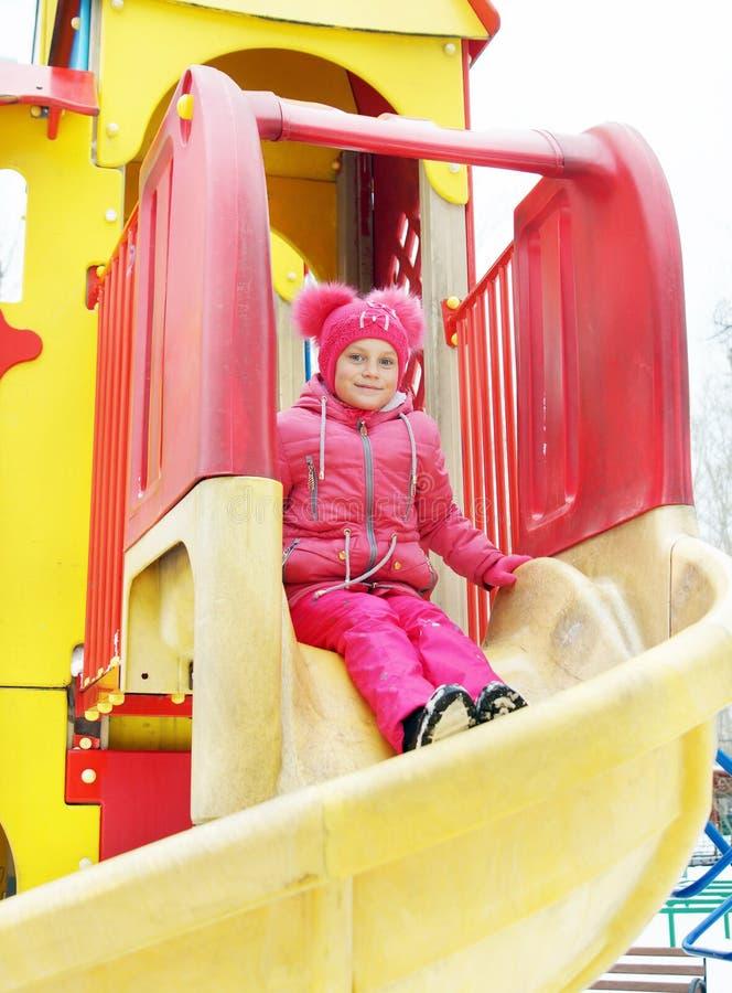 A menina monta para baixo de uma corrediça no campo de jogos fora fotos de stock royalty free